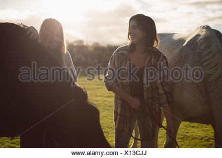 Women standing with horse in farmland on a sunny day - Stock Photo