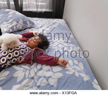 Girl sleeping on bed - Stock Photo