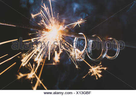Wedding Rings hang on a sparkler as it burns down illuminating the rings - Stock Photo