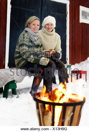 Sweden, Portrait of mother sitting with teenage girl (14-15) on bench in winter - Stock Photo