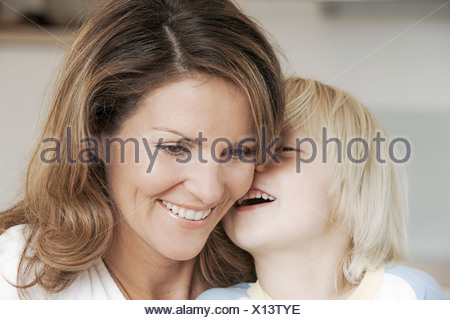 Blonde son whispering into his mothers ear - Stock Photo