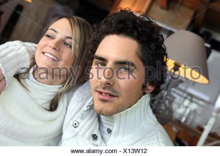 Couple sitting comfortably on sofa - Stock Photo