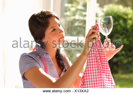 Woman carefully polishing wine glass - Stock Photo