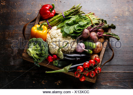 Fresh raw vegetables in wooden box on wooden background - Stock Photo