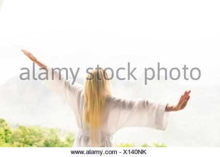 Woman in bathrobe overlooking landscape - Stock Photo