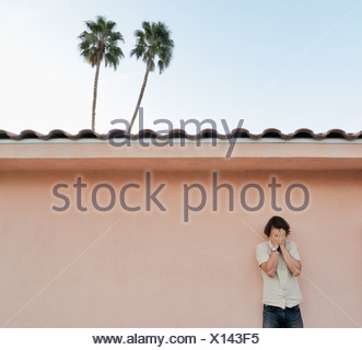Man covering his face outdoors