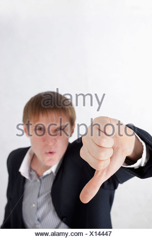 Young man frowning and making thumbs down - Stock Photo
