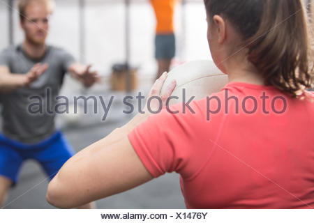 Rear view of woman throwing medicine ball towards man in crossfit gym - Stock Photo