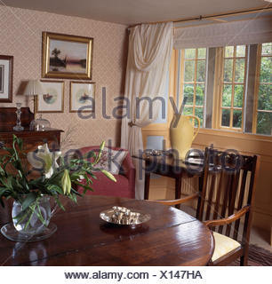 Vase Of White Lilies On An Antique Table In A Nineties Cottage Dining Room With Patterned
