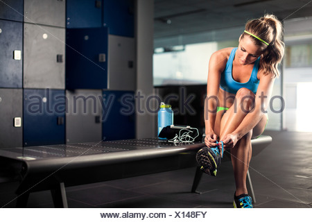 Young woman tying trainer lace in gym - Stock Photo