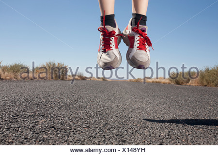 USA, Arizona, Winslow, Human feet in sport shoes jumping - Stock Photo