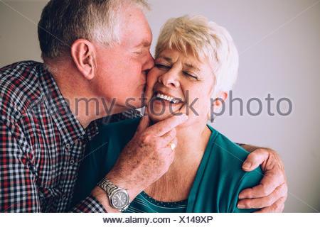 Senior man kissing wife on cheek - Stock Photo