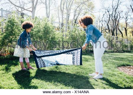 Side view of mother and daughter laying out blanket on grass - Stock Photo