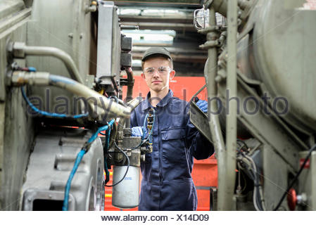 Portrait of young apprentice locomotive engineer in train works - Stock Photo