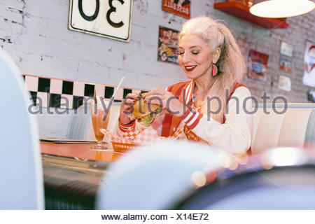 Mature woman in baseball jacket eating burger in 1950's diner - Stock Photo
