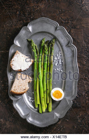 Cooked green asparagus with half boiled egg and sliced bread served with sea salt on vintage metal plate over brown texture background. Top view, fine - Stock Photo