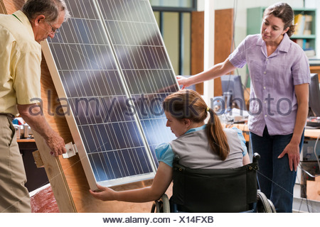 Professor explaining mounting of photovoltaic module to engineering students - Stock Photo