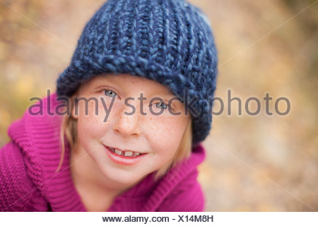 A girl in a knitted hat, and magenta jumper with a folded collar. - Stock Photo