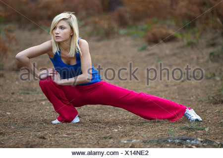 Woman stretching in woods - Stock Photo