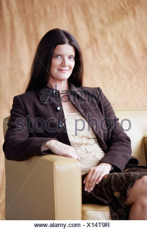 Portrait of a mature woman sitting in an armchair - Stock Photo