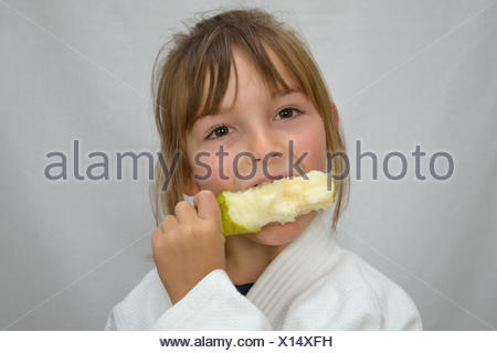 little girl biting pear - Stock Photo