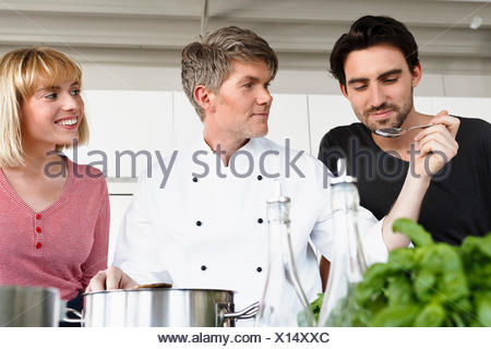Chef and couple in kitchen tasting food - Stock Photo