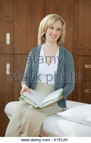 masseuse reading while waiting for a patient - Stock Photo