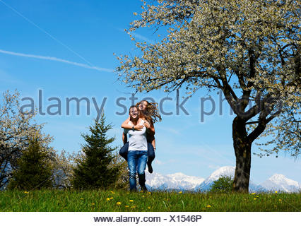 Man carrying a woman, smiling, in front of a flowering tree in the spring, Tyrol, Austria - Stock Photo