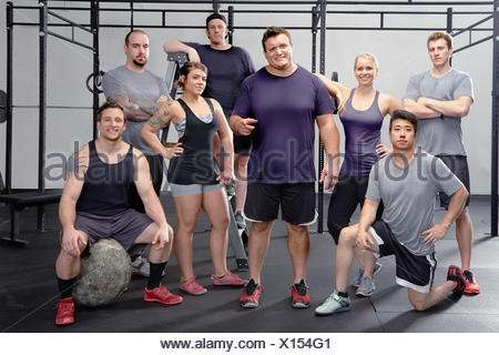 Portrait of eight people in gym - Stock Photo