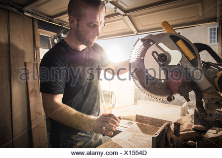 Male carpenter working with a rotary saw in workshop - Stock Photo