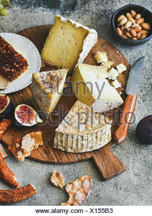 Cheese platter with cheese assortment, figs, honey, fresh bread and nuts on board over grey concrete background. Party or gathering eating concept - Stock Photo
