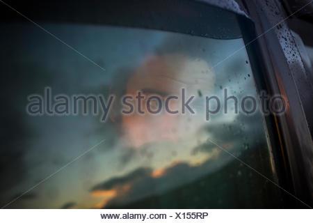 A man sitting in a car looking out. Reflections of the sunset sky on the window. - Stock Photo