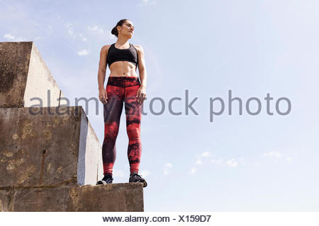 Young female free runner looking out from top of sea wall - Stock Photo