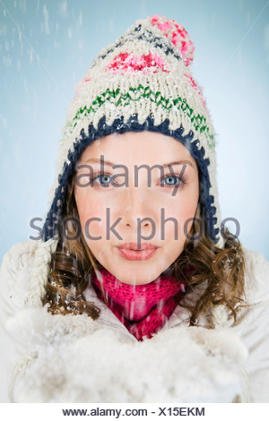 A young woman holding a handful of snow - Stock Photo
