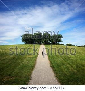 Man standing on road on grassy field against sky