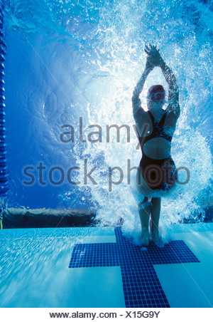 Rear view of female swimmer in competition - Stock Photo
