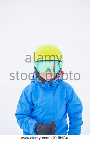 Smiling boy (10-11) wearing helmet and ski goggles against snow - Stock Photo