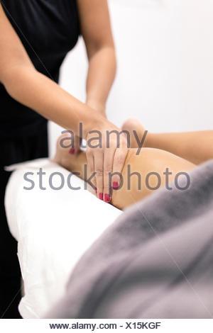 Young woman receiving a leg massage - Stock Photo