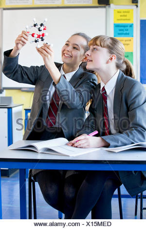 Smiling high school students examining molecule model in science class - Stock Photo