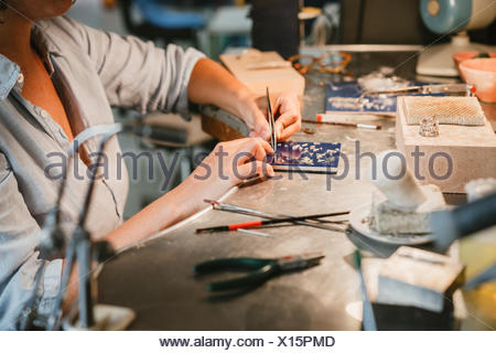 Female jeweller picking up silver metal with tweezers at workbench - Stock Photo