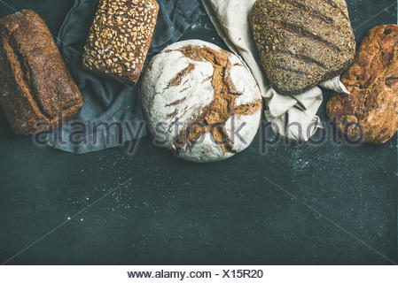 Various bread selection flat-lay. Top view of Rye, wheat and multigrain rustic bread loaves over black background, copy space - Stock Photo
