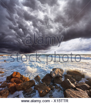 The storm cloud over the raging surf - Stock Photo