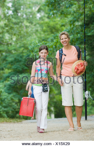 Portrait of a mature woman walking with holding hands of her daughter - Stock Photo