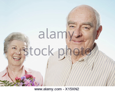 Senior man looks pleased that she likes the flowers - Stock Photo