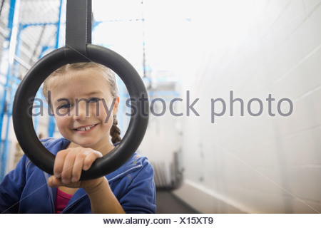 Portrait of girl looking through gymnastic ring - Stock Photo