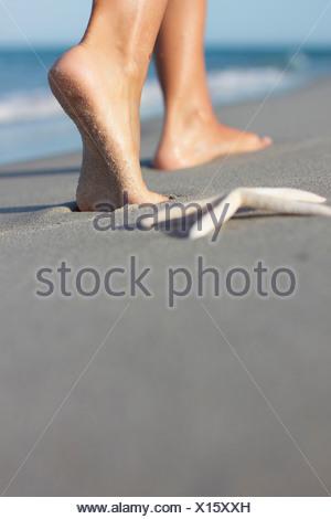 Italy, Sardinia, Woman's feet walking on sandy beach - Stock Photo