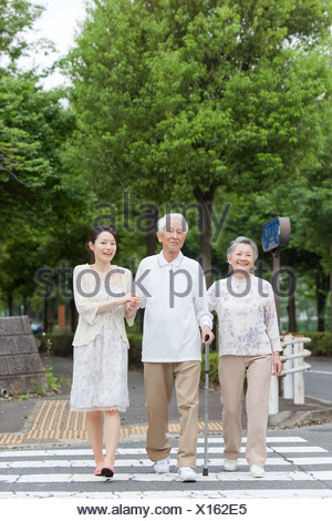 Japan, Tokyo Prefecture, Young woman with parents crossing road - Stock Photo
