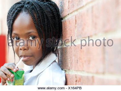 Portrait of girl drinking juice through straw outside school, Johannesburg, Gauteng Province, South Africa - Stock Photo