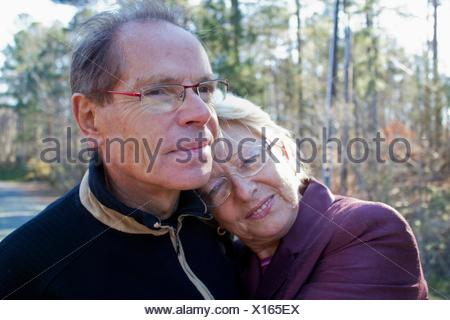A caucasian couple in their 60´s taking a walk around a lake a sitting on a swing, enjoying retirement. - Stock Photo
