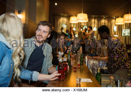 Couple talking and drinking at bar - Stock Photo